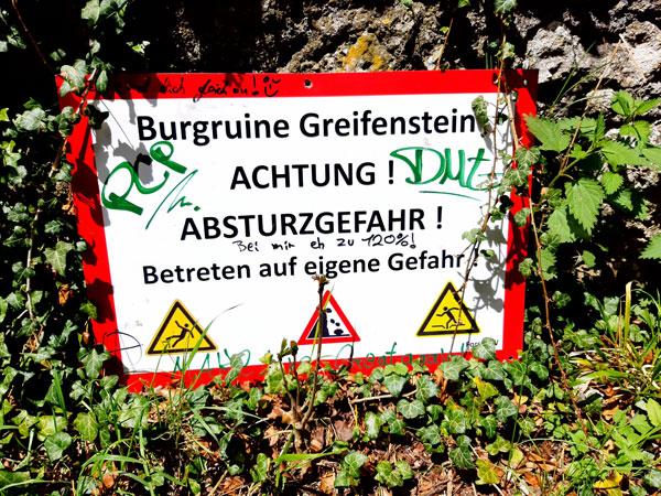 """Schild mit der Aufschrift """"Burgruine Greifenstein - Achtung! Absturzgefahr! Betreten auf eigene Gefahr!"""""""