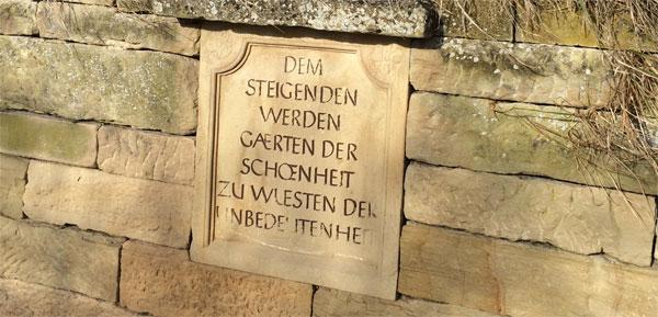 """Steintafel mit der Inschrift """"Dem Steigenden werden Gärten der Schönheit zu Wüsten der Unbedeutenheit."""""""