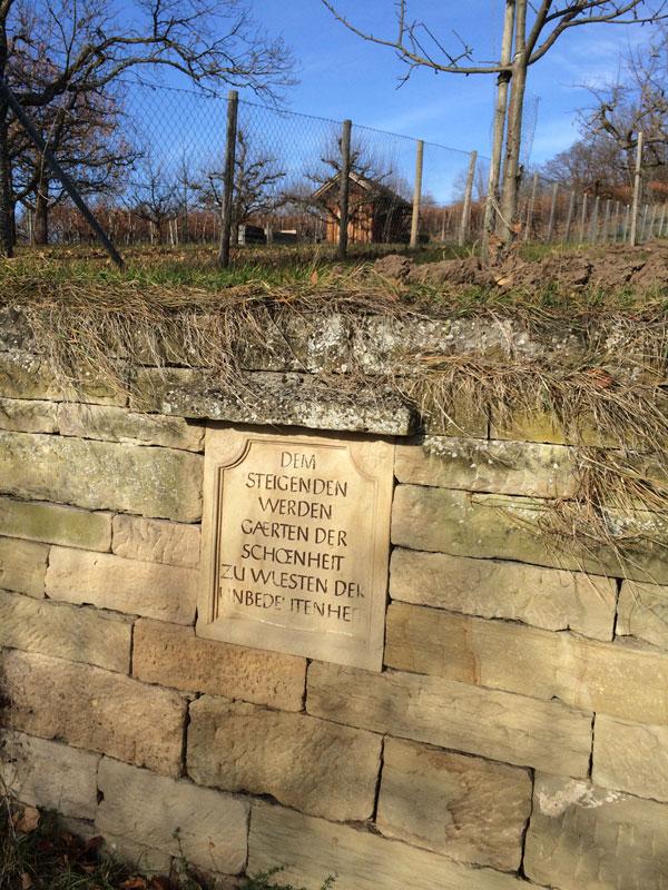 """Steintafel in Mauer mit der Inschrift """"Dem Steigenden werden Gärten der Schönheit zu Wüsten der Unbedeutenheit."""""""