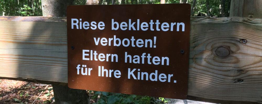 """Schild mit Aufschrift """"Riese beklettern verboten! ELtern haften für Ihre Kinder."""""""